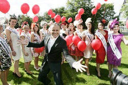 Photograh of a group of Rose of Tralee contestants with sashes and balloons. Daithi O Sea is standing in front of them, his arms making a jazz hands motion.
