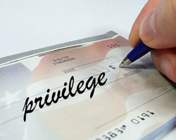 photo of cheque with 'privilege' written on it. A hand can be seen writing on the cheque with a pen.