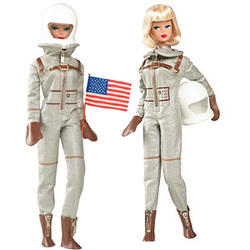 Two 1960s Barbie dolls dressed up as astronauts. One is holding a USA flag, the other is holding her helmet to her side so that her face and blonde bobbed hair is visible.