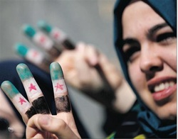 A woman holds up three fingers which are painted with the Syrian flag.